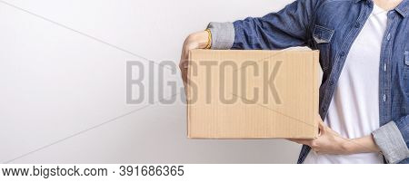 Asian Delivering Package With Brown Box Isolated On Grey Background , Closeup Hands Of Delivery Hold