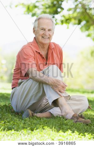 Senior man sitting outdoors poster