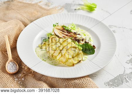 Fish with Cucumber Scales and Cabbage Steak. Garnished with Fresh Greens. Sackcloth and white plated on ligh table