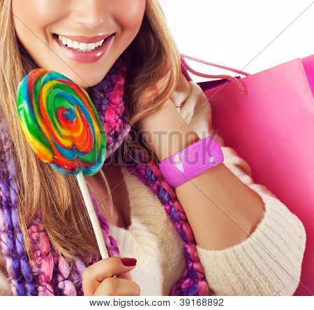 Picture of pretty woman eating sweet candy, cute girl with perfect smile holding pink shopping bag and licking big colorful lollipop, Christmas present, New Year holiday, sweets shop sale concept
