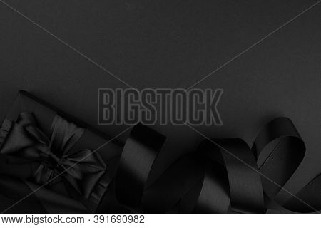 Black Friday Gift, Paper Box With Silk Ribbon Bow On Black Paper Background With Copy Space For Text