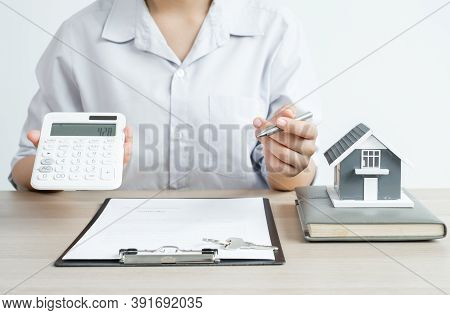 Agents Working In Real Estate Investment There A House Model Hold A Pen And A Calculator And Home Le