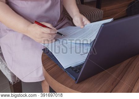 Woman's Hand Holding Red Pen Checking On Blurred Essay Spelling Over Laptop