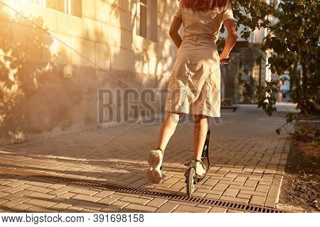 Girl In Dress Riding On Scooter On Street. Sunset Light Fall On Exterior. New Emotion And Leisure Ti
