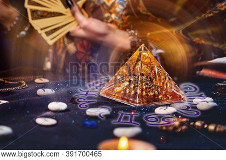 Magic Divination And Esotericism. Magic Glass Pyramid With A Magical Glow. In The Background, A Fort