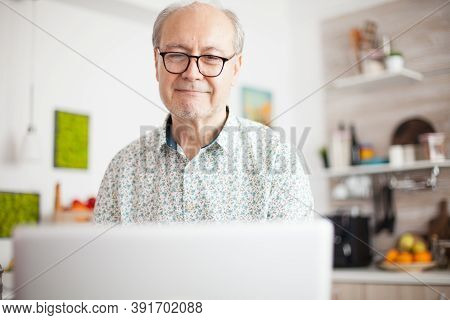 Retired Man Smiling While Watching A Movie On The Laptop. Daily Life Of Senior Man In Kitchen During