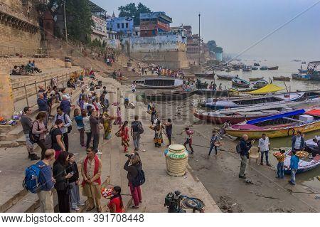 Varanasi, India - November 07, 2019: Tourists At The Ghats Of The River Ganges In Varanasi, India