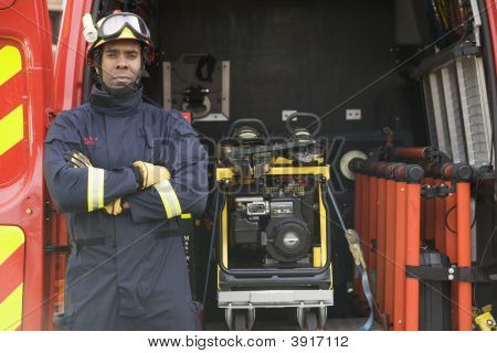 Rescue Worker Standing By Open Back Door Of Rescue Vehicle
