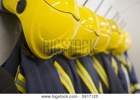 Line Of Firefighting Uniforms Hanging Neatly On Wall Hooks (Depth Of Field)
