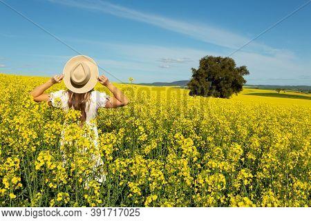 Woman In White Dress In Field Of Golden Canola Flowering In Spring In The Rural Fields Of Australia