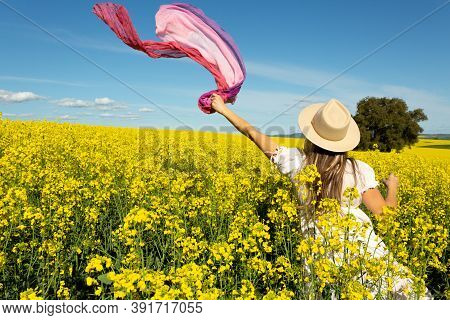 Woman In White Sun Dress In A Field Of Flowering Golden Canola
