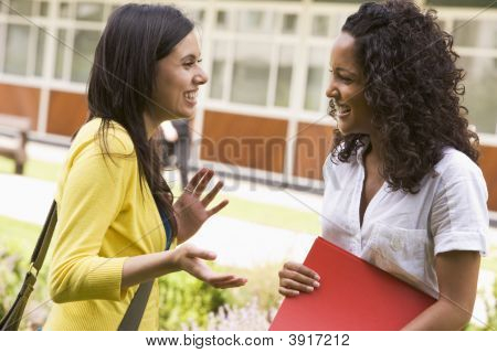Two Students Standing Outdoors Talking