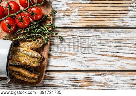 Fried Smelt In The Pan On The Table With Tomatoes And Pepper. White Background. Top View. Copy Space