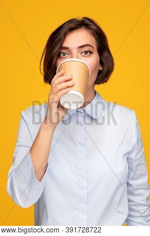 Young Woman In Blouse Sipping Takeaway Drink And Looking At Camera In Morning Against Yellow Backgro