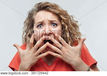 I'm Afraid. Image Of Scared Blonde Girl With Curly Hair In Casual T Shirt Covering Her Mouth With Ha