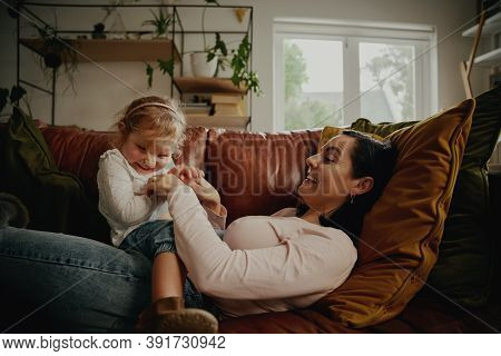 Cheerful Mother And Daughter Tickling And Playing At Home On Couch
