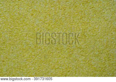 Yellow Ocher Stucco Texture On Exterior Wall With Fine Grains. Yellow Sandpaper Background Macro