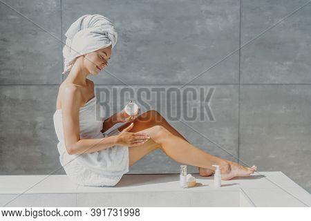 Horizontal Shot Of Pretty Woman With Slender Legs Puts Moisturising Cream On Healthy Skin Enjoys Bea