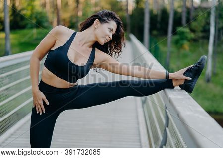 Sporty Slim Brunette Woman Dressed In Cropped Top And Leggings Stretches Legs On Bridge Does Warm Up