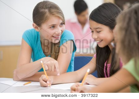 Students In Class Writing And Talking With Teacher In Background (Selective Focus)