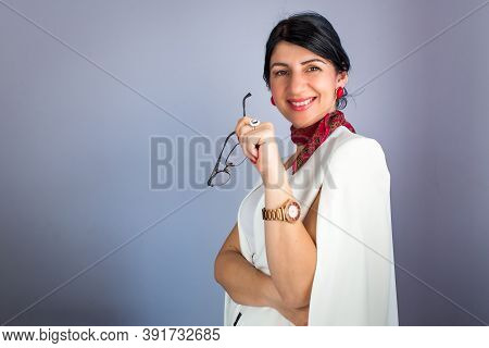 Portrait Of Elegant Brunette Woman Holding Eyeglasses And Smiling. Isolated On Blue Background