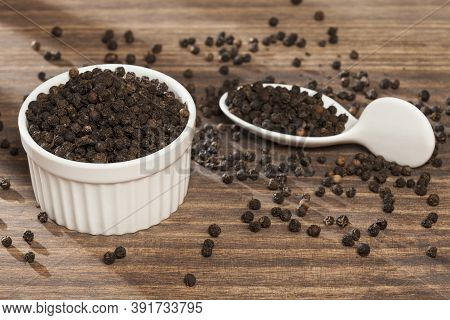 Piper Nigrum - Black Peppercorns; Photo On Dark Wooden Background.