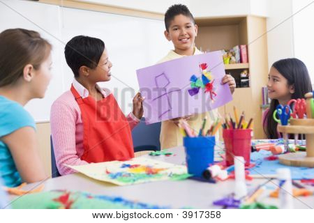 Student Showing Teacher And Classmates His Artwork (Selective Focus)