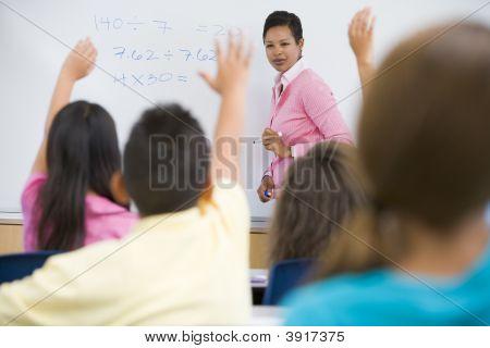 Estudiantes en la clase de voluntariado para maestro en el tablero delantero (enfoque selectivo)