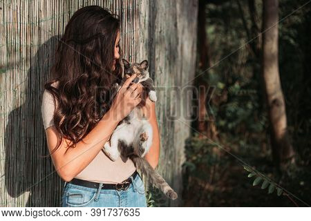 Beautiful Young Girl Holding A Calico Cat. Outdoors Photo, Copy Space