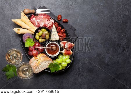 Antipasto plate with prosciutto, cheese, figs and grapes. Appetizer board. Top view with copy space