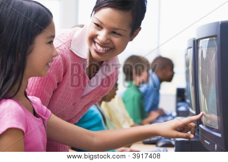 Teacher helping Student an Computer-terminal mit Studenten im Hintergrund (Tiefe Feld/High Key)