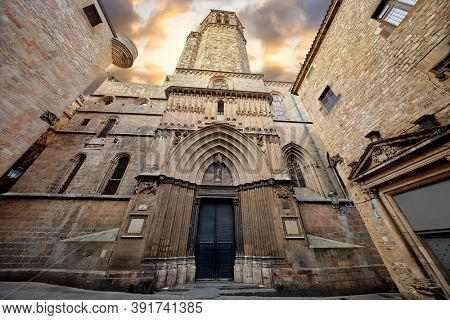 Gothic cathedral in Barcelona, Catalonia, Spain. Entrance in Barcelona Cathedral with tower. Ancient architecture of old town with medieval houses. Blue evening sky with clouds and antique street.