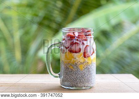 Almond Milk Chia Pudding With Fresh Strawberries And Mango In A Glass Jar Mug. Vegan Raw Breakfast.