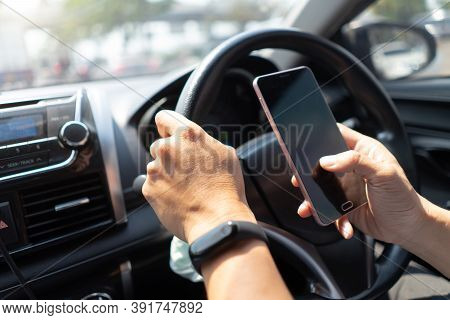 Man Driving Car Using Mobile Phone Texting Message. Driver Holding Smart Phone While Driving Car On