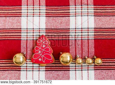 Creative Christmas Composition With Red Gingerbread Cookie And Christmas Balls. Red Woolen Checkered