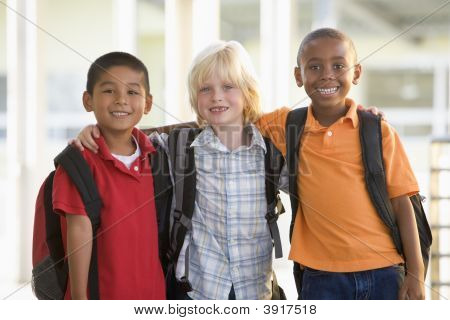 Three students outside school standing together smiling (selective focus) poster