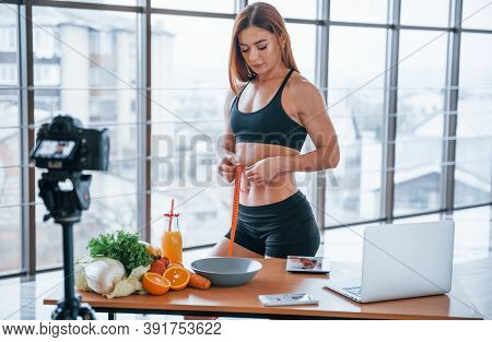 Female Vlogger With Sportive Body Standing Indoors With Measuring Tape Near Table With Healthy Food.