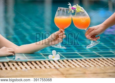 Woman Dink A Cocktail Glass Of Orange Juice With Friend At Swimming Pool. Summer Holiday And Relax A
