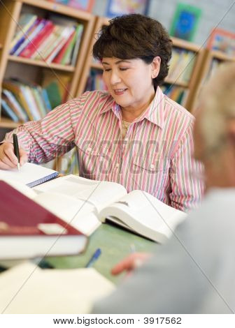 Man And Woman Sitting In Library Reading Books (Selective Focus)