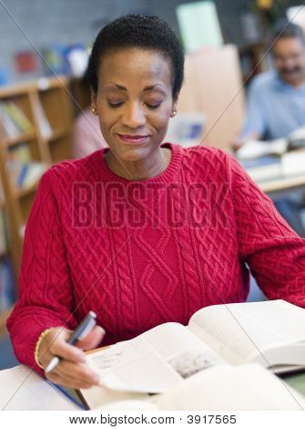 Woman Sitting In Library With A Book And Notepad (Selective Focus)