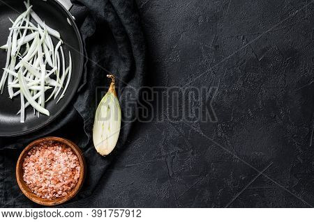 Sliced Shallot In A Pan, Cooking Fried Onions. Black Background. Top View. Space For Text