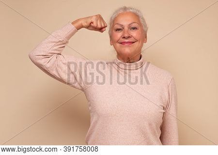 Elderly Happy Senior Woman Showing Her Muscles Being Self Confident.