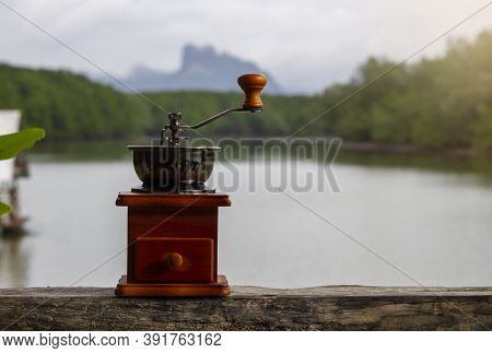 Hand Crank Coffee Grinder, Brown, Placed On A Wooden Floor. The Backdrop Is A River With Sunlight Sh