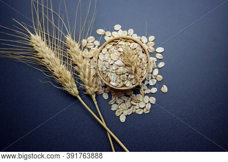 Barley Flakes In A Round Wooden Bowl And Spikelets Of Wheat On A Gray Background.