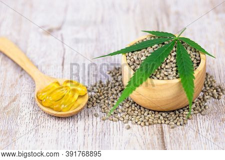 Cannabis Seeds In A Wooden Cup, Cannabis Leaves Are Placed On Top. And Extracted Cannabis Oil Into T