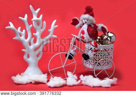 Red And White Christmas Composition With Small Toy Santa On Tricycle, White Tree And Snow Isolated O