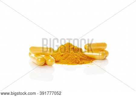 Turmeric (curcumin) Powder Heap And Capsules Isolated On White Background. Anti-inflammatory Nutriti