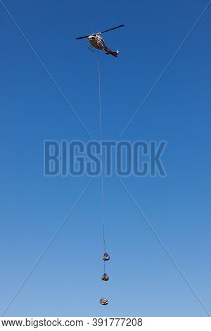 Prospect,  Oregon / Usa - September 9, 2014:  A Supply Helicopter Carrying Three Parcels Comes In Fo