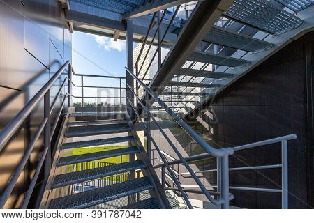 External Metal Staircase On A Modern Building. Solar Lighting, Summer Day