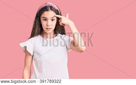 Cute hispanic child girl wearing casual white tshirt pointing unhappy to pimple on forehead, ugly infection of blackhead. acne and skin problem